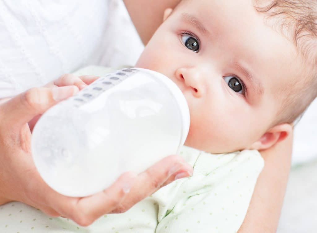 Close-up of a baby drinking milk in his mother's arms at home